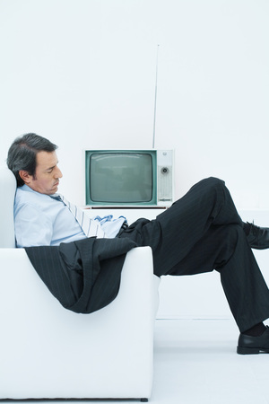 burned out: Businessman taking a nap in armchair, slouching with legs crossed, side view LANG_EVOIMAGES