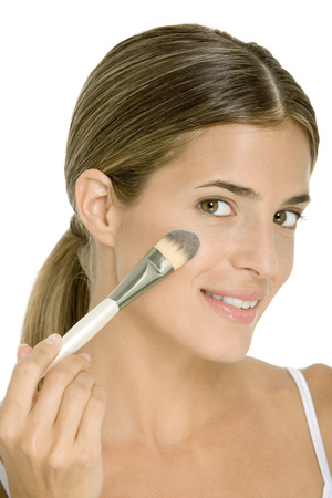 Woman applying face powder with make-up brush, smiling at camera LANG_EVOIMAGES