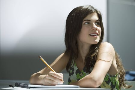 distractions: Teenage girl writing in notebook, dreamily looking away LANG_EVOIMAGES