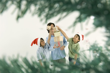Young man holding tall stack of Christmas gifts, boys placing more gifts on top of stack LANG_EVOIMAGES