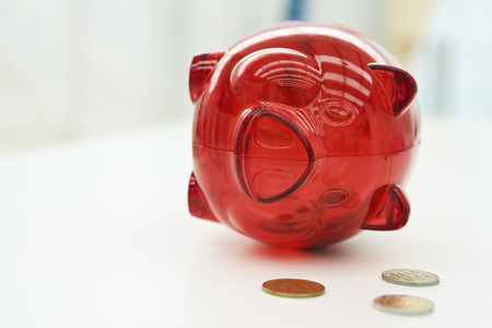 Piggy bank lying on side, coins nearby