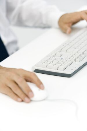 Businessman using keyboard and mouse, cropped view