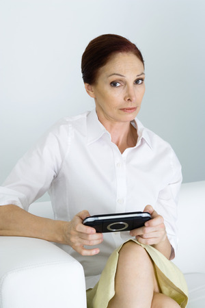 Mature woman holding handheld video game, looking at camera with eyebrow raised LANG_EVOIMAGES