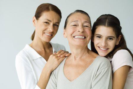 Multi-generational family smiling at camera, portrait
