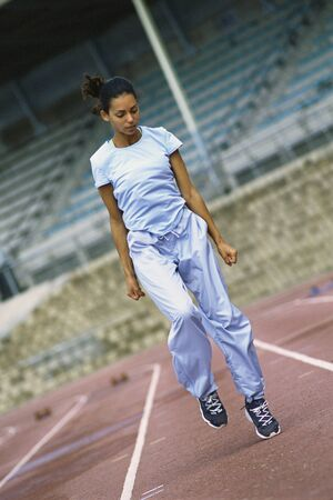 Woman jogging in place on track LANG_EVOIMAGES