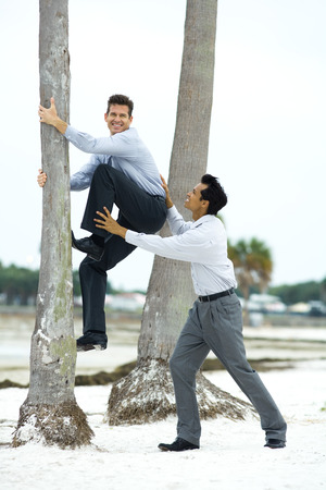 overcoming adversity: Businessman climbing palm tree with associates help