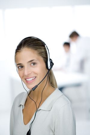 Woman wearing headset, smiling at camera, portrait LANG_EVOIMAGES