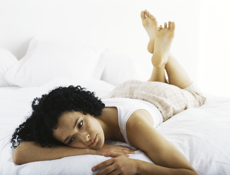 Woman lying on stomach daydreaming