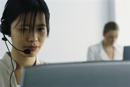 Young woman wearing headset and using computer LANG_EVOIMAGES
