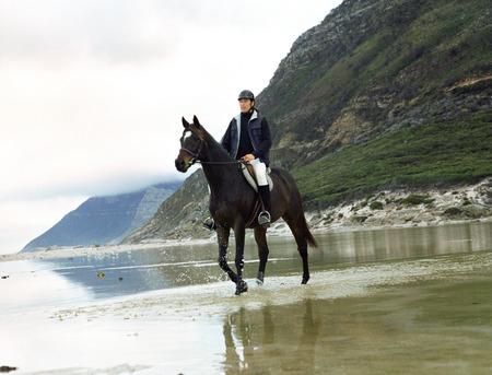 Man riding horse through water