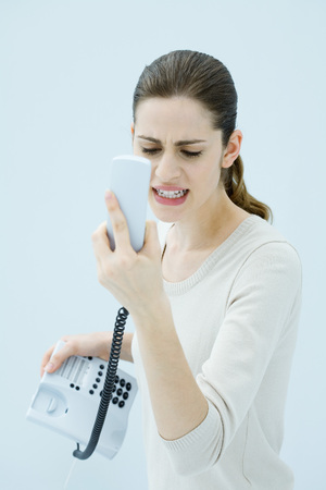 Young woman shouting at landline phone, receiver in hand
