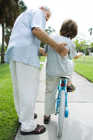 Senior man helping his grandson learn to ride a bicycle