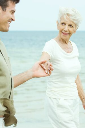 daily life: Senior woman walking hand in hand with adult son by water, smiling at each other