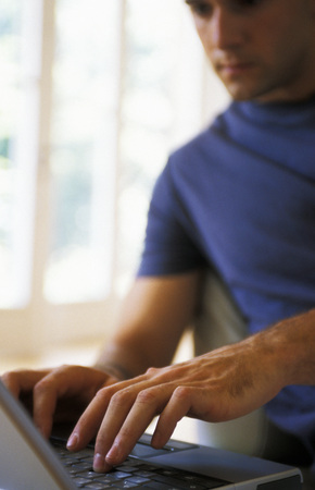 Man typing on laptop, focus on hands