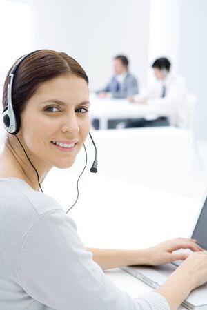 Woman wearing headset, working at desk, smiling over shoulder at camera LANG_EVOIMAGES