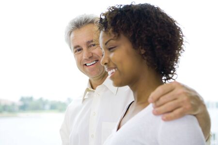 southern european descent: Mature man with arm around young womans shoulder, both smiling