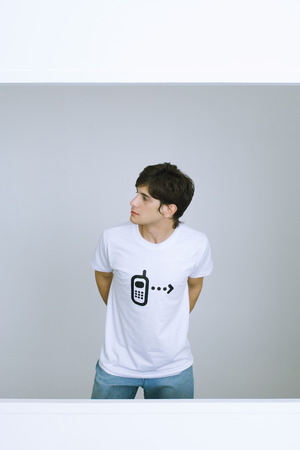 curiousness: Young man wearing tee-shirt with cell phone graphic, looking away, hands behind back