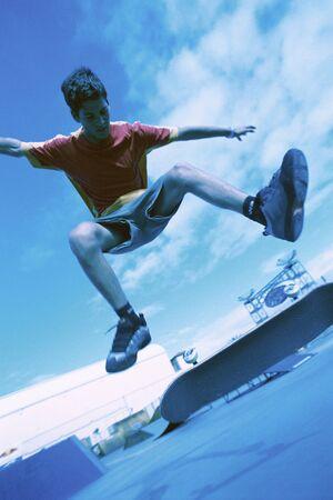 Skateboardfahrer, der Trick mitten in der Luft, niedrige Winkelsicht tut LANG_EVOIMAGES