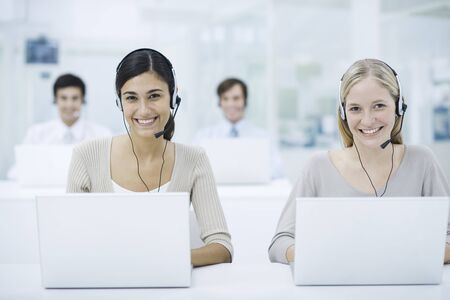 Telemarketers working in call center, smiling LANG_EVOIMAGES