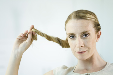 distractions: Woman twisting hair, smiling at camera, portrait