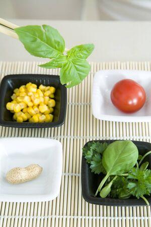 Chopsticks holding sprig of herb over several dishes of food LANG_EVOIMAGES