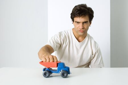 puckered lips: Man playing with toy dump truck, looking at camera with furrowed brow LANG_EVOIMAGES