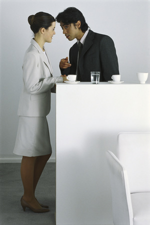 Male and female colleagues having coffee break together, gossiping