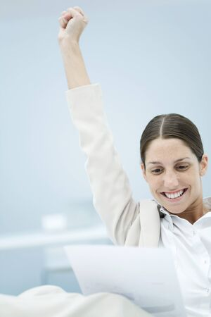 Young businesswoman reading document, raising one arm in the air