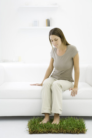 Woman sitting on loveseat indoors, bare feet resting on patch of grass