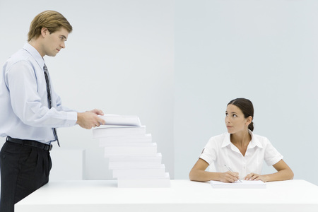 Man adding to large stack of documents on professional womans desk