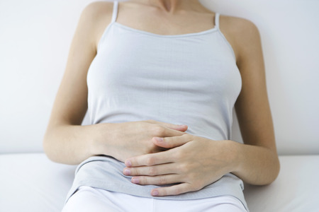 unease: Woman holding stomach, cropped view