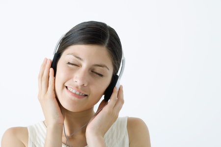 impassioned: Young woman listening to headphones, smiling, eyes closed LANG_EVOIMAGES