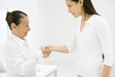 Senior woman shaking young womans hand, side view LANG_EVOIMAGES