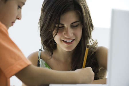 Tutor helping elementary school student with homework LANG_EVOIMAGES