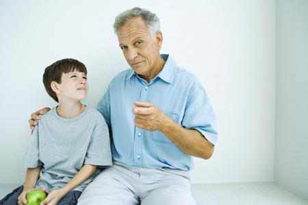 Senior man sitting with grandson, his arm around his shoulder