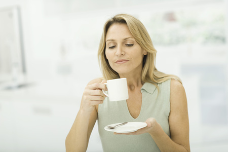 Woman holding coffee cup, smiling