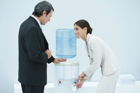 Two professionals chatting beside water cooler, woman filling disposable cup