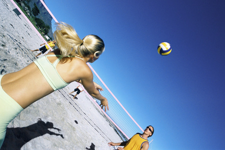 Female preparing to volley ball to teammate