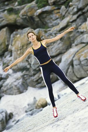Young woman doing jumping jacks outdoors