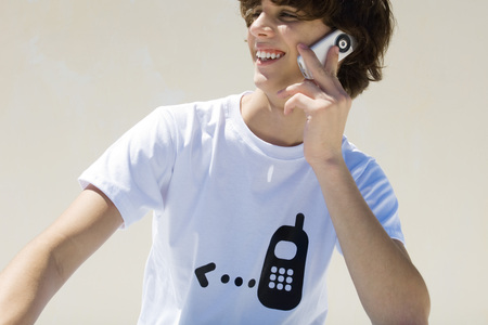 Teenage boy wearing tee-shirt printed with cell phone graphic, using cell phone, smiling LANG_EVOIMAGES