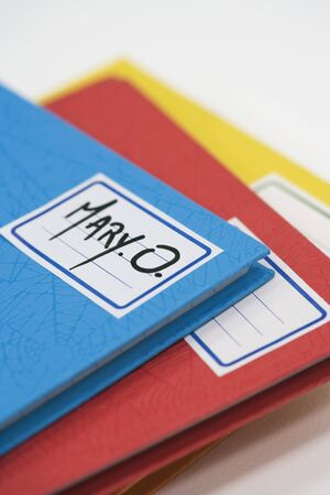 Pile of school notebooks with name written on label
