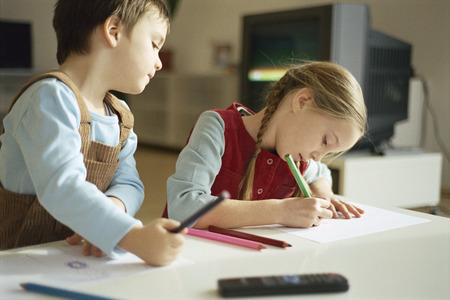 Siblings drawing with colored pencils, little boy pausing to look over sisters shoulder