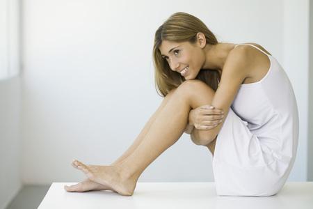 Woman in slip sitting on table, hugging knees, smiling LANG_EVOIMAGES