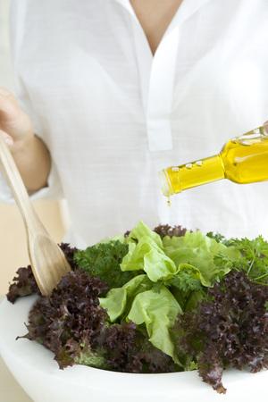 Woman preparing salad, pouring olive oil dressing LANG_EVOIMAGES