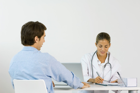 Female doctor sitting across from male patient at desk, writing down notes