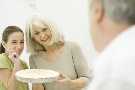 Grandmother and granddaughter offering pie to man in foreground, smiling LANG_EVOIMAGES