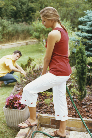 Woman watering garden with hose, husband crouching in background