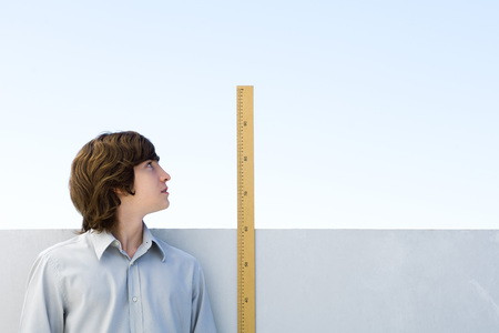 centimetres: Young man measuring his height with ruler