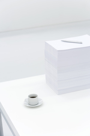 burned out: Coffee cup and large stack of documents on desk