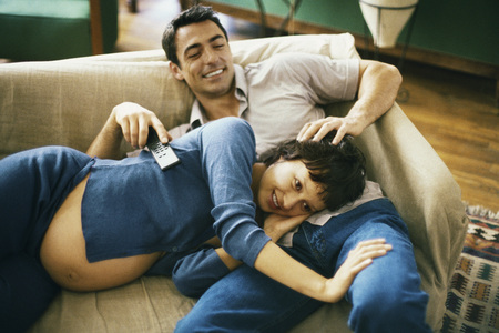 Expecting couple relaxing on sofa, watching TV, woman resting head in mans lap LANG_EVOIMAGES